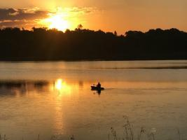 Kayaker near Allemansratt on North Center Lake at sunset